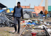LASSERRE A man walks through a makeshift camp set up by migrants in Calais western France on May 17 2014 As border controls have relaxed across...