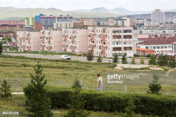 A man walks through a park as housing stands in the background in Darkhan Mongolia on Monday Aug 14 2017 Mongolia desperate to make more of its...