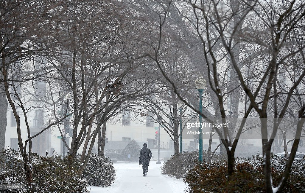 A man walks through a park as snow continues to fall near the U.S. Capitol on March 3, 2014 in Washington, DC. The Washington area has been hit by repeated snow storms throughout the winter.