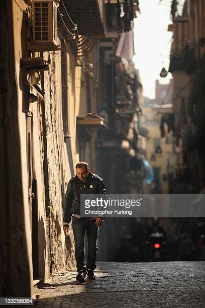 A man walks through an alleyway of densely populated Naples on November 18 2011 in Naples Italy Italy's new Prime Minister Mario Monti and his new...