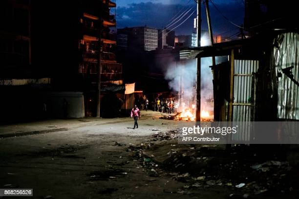 A man walks through an empty street while protesters gather around a burning barricade in the Mathare slums in Nairobi on October 30 2017 during...