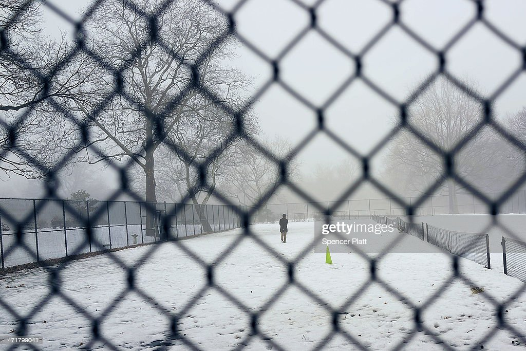 A man walks through Brooklyn's Fort Greene Park in the fog on February 21, 2014 in New York City. After weeks of bitter cold weather and heavy snow, New York and much of the Northeast got a break from winter with warming temperatures. The forecast calls for temperatures to remain warm through the weekend before falling back down next week.