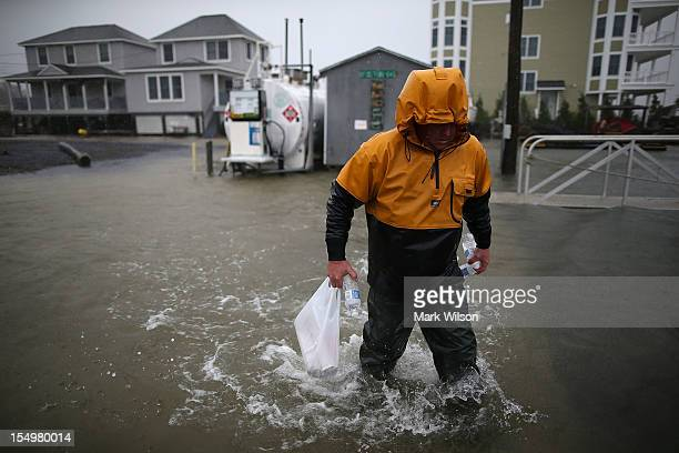 A man walks through flood waters caused by Hurricane Sandy on October 29 2012 in Cape May New Jersey Later today the full force of Hurricane Sandy is...