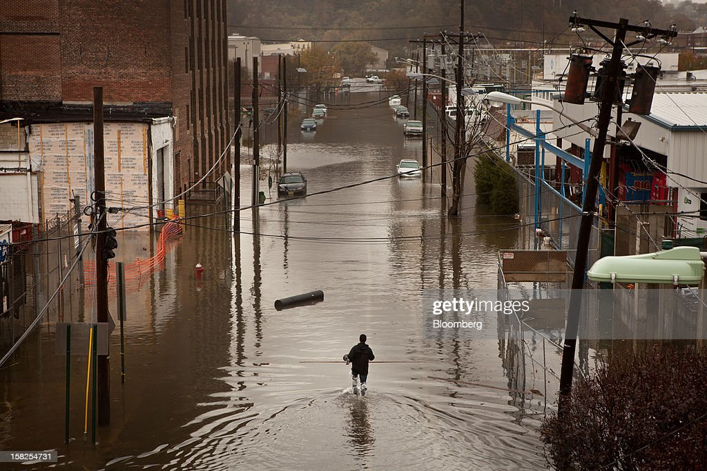 'BEST PHOTOS OF 2012' (): A man walks through flood waters in Hoboken, New Jersey, U.S., on Tuesday, Oct. 30, 2012. The Atlantic storm Sandy left a landscape of devastation across much of New Jersey, tearing apart seaside resort towns, ripping houses from foundations and littering the turnpike with rail cars and debris. Photographer: Emile Wamsteker/Bloomberg via Getty Images