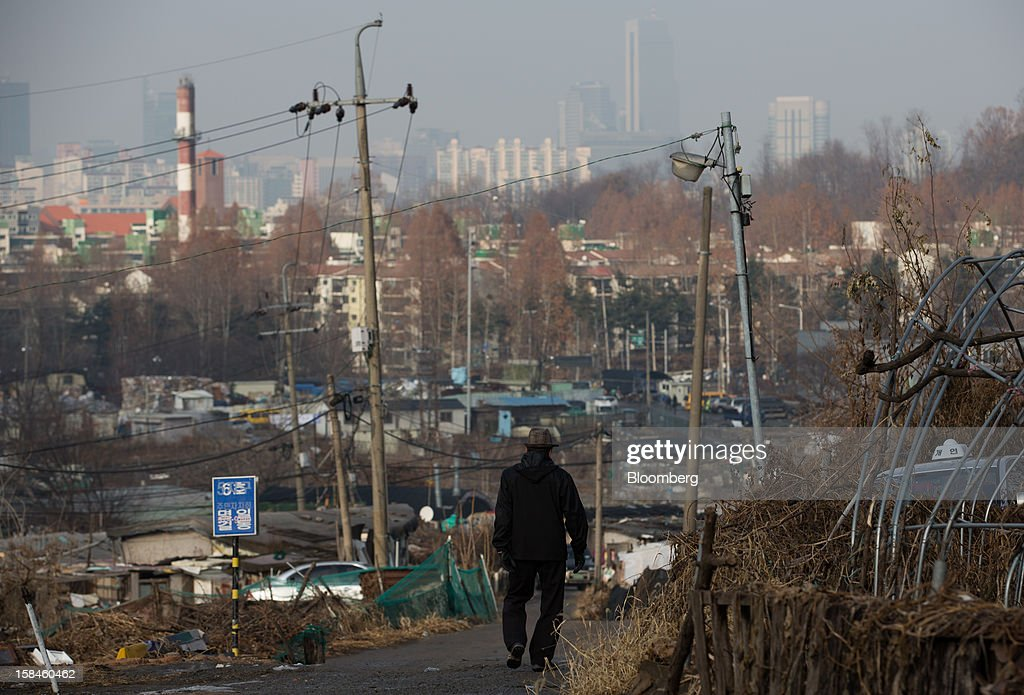 A man walks through Guryong village as high rise residential buildings stand in the background in the Gangnam district of Seoul, South Korea, on Sunday, Dec. 16, 2012. South Koreans vote on Dec. 19 to replace President Lee Myung Bak, whose five-year term ends in February. Photographer: SeongJoon Cho/Bloomberg via Getty Images