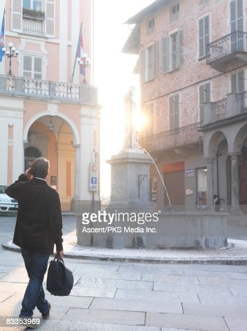 Man walks through historic centre, on cell phone : Stock Photo