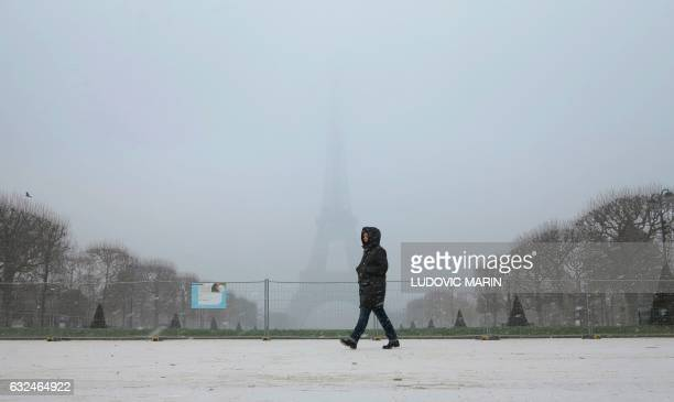 A man walks through light snowfall in front of the Eiffel Tower on January 23 2017 in Paris / AFP / Ludovic MARIN