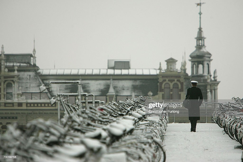 A man walks through past bicycles covered in snow on February 8, 2007, in Amsterdam, Netherlands. The Dutch transport system has suffered delays across the country, with an expected 5-10 centimetres due to fall, according to The Dutch Meteorological Institute.