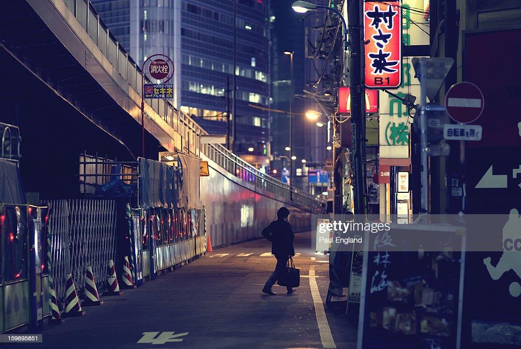 CONTENT] A man walks through Shinjuku in the evening.