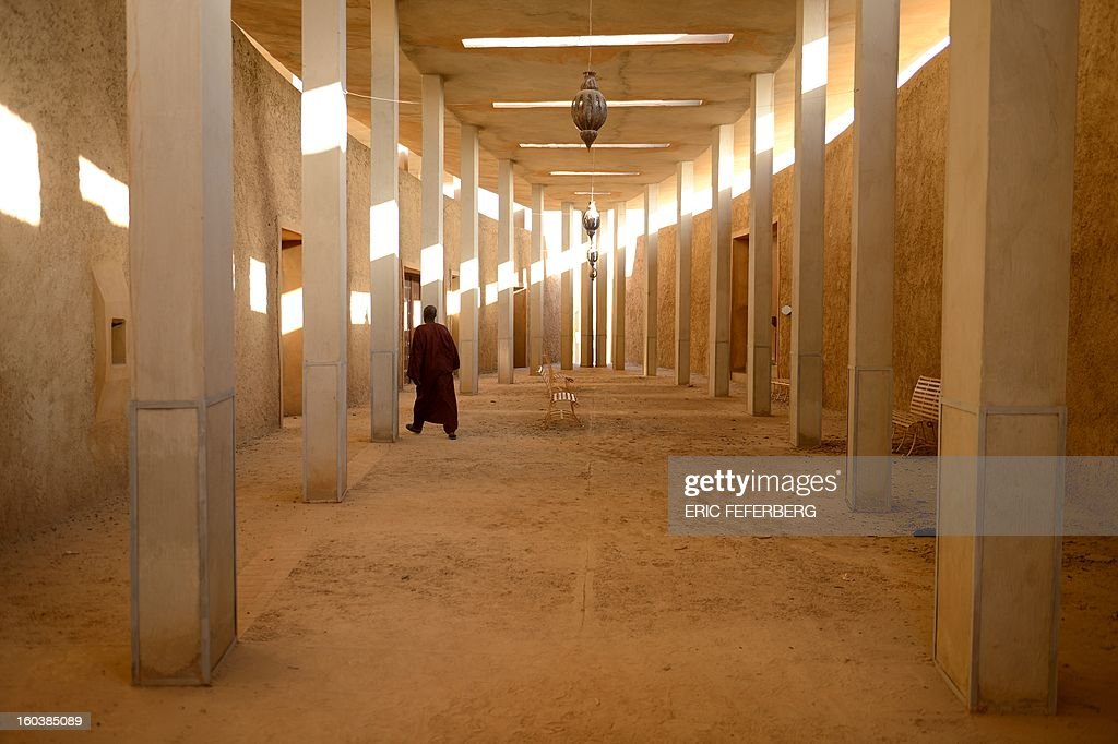 A man walks through the Ahmed Baba institute of higher learning and islamic research in Timbuktu on January 29, 2013. French-led forces seized yesterday Mali's fabled desert city of Timbuktu in a lightning advance north as fleeing Islamists torched the building housing priceless ancient manuscripts. Mayor Ousmane confirmed the fire at the Ahmed Baba Centre which housed between 60,000 and 100,000 manuscripts, according to Mali's culture ministry. FEFERBERG