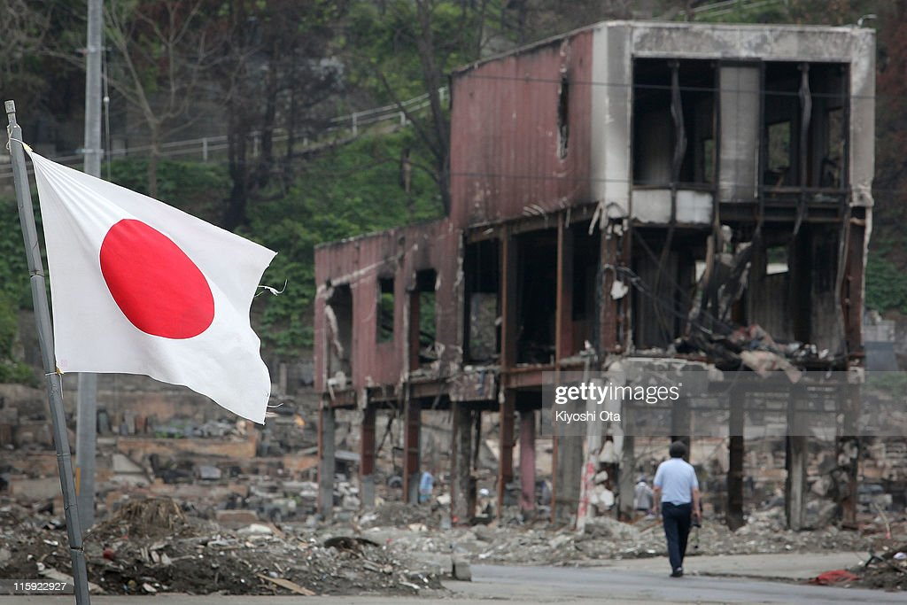 A man walks through the debris as the Japanese national flag flies on June 12, 2011 in Otsuchi, Iwate, Japan. Japanese government has been struggling to deal with the earthquake and tsunami as well as the troubled Fukushima Daiichi Nuclear Power Plant. The fear of infectious disease outbreak is mounting due to the humid rainy season and delay of the debris clearing.