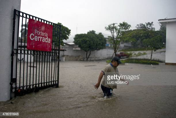 A man walks through the flooded entrance of the Children's Clinic Foundation Club Noel in Cali Colombia on March 12 during heavy rains The IDEAM...