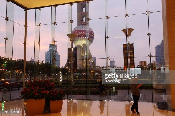 A man walks through the foyer of a commercial building as the Oriental Pearl Tower stands behind a glass window at dusk in the Lujiazui district of...