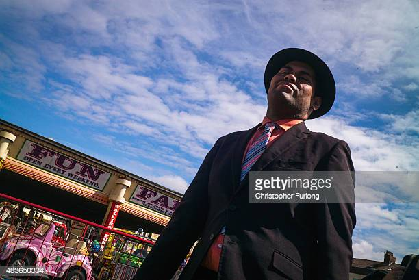 A man walks through the fun fair as daytrippers and children on the Summer break from school enjoy the warm weather at New Brighton beach on August...