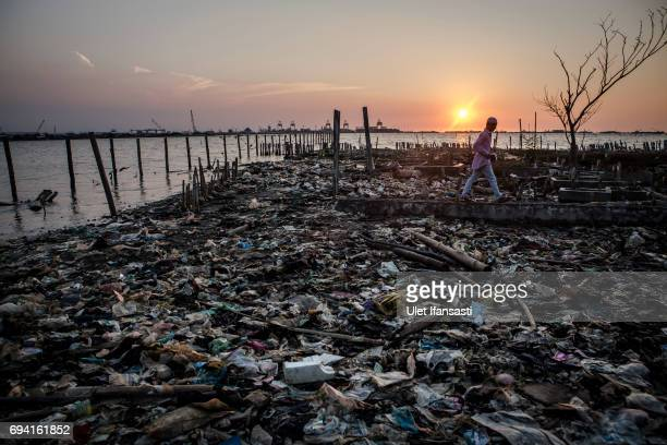 A man walks through the garbage as he head to the public cemetery for pray which surrounded by rising sea levels on June 8 2017 in Semarang Indonesia...