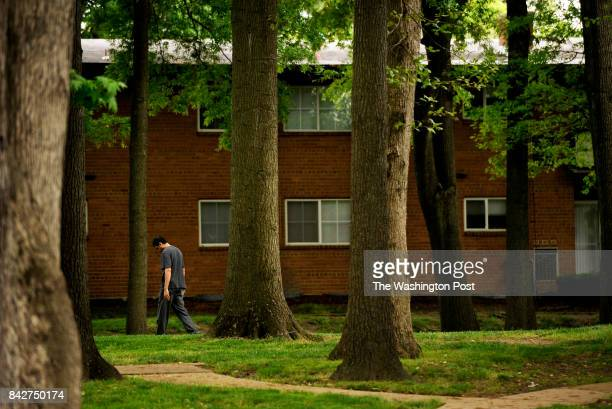 A man walks through the grounds of Meadow Creek Apartments on Tuesday May 01 2012 in Alexandria VA Many residents in the Beauregard Corridor are...