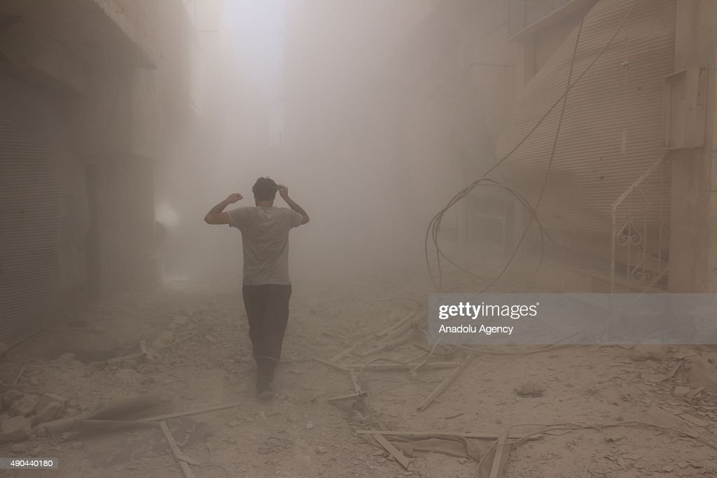 A man walks through the smoke after an air-strike staged by Syrian regime forces to the opposition residential areas in Duma district in the Eastern Ghouta area of Damascus, Syria on September 28, 2015.