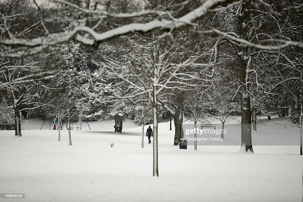 A man walks through the snow in The Pavilion Gardens on January 21, 2013 in Buxton, United Kingdom. The Met Office has issued a red weather warning for parts of the Uk and advising against all non-essential travel as up to 30cm of snow is expected to fall in some areas today. The adverse weather has closed nearly 5,000 schools and caused many airports to cancel flights.