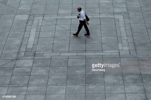 A man walks through the Umeda Sky Building in Osaka Japan on Wednesday June 24 2015Japanese consumer prices rose fractionally in May as central bank...