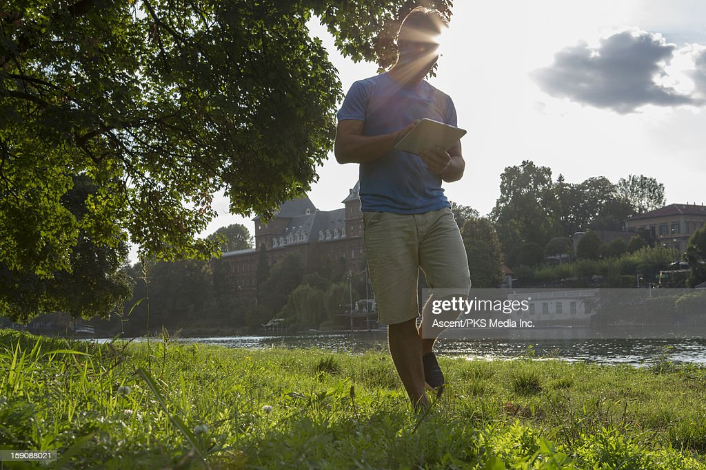 Man walks through urban park, uses digital tablet : Stock Photo