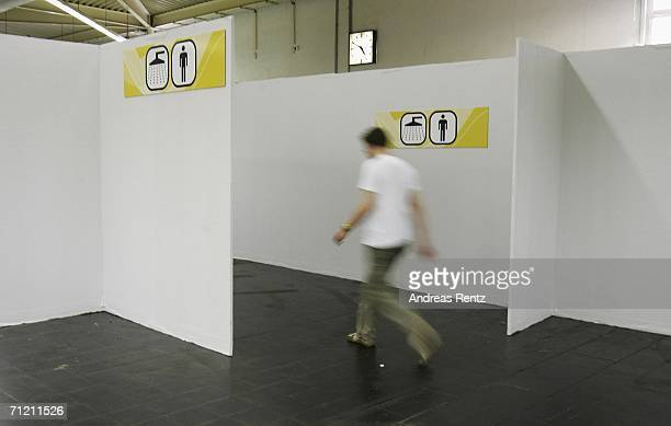 A man walks to a shower cabin inside the 'Fan Camp' on June 15 2006 in Dortmund Germany 'Fan Camp' offers accomodation for up to 4000 people during...