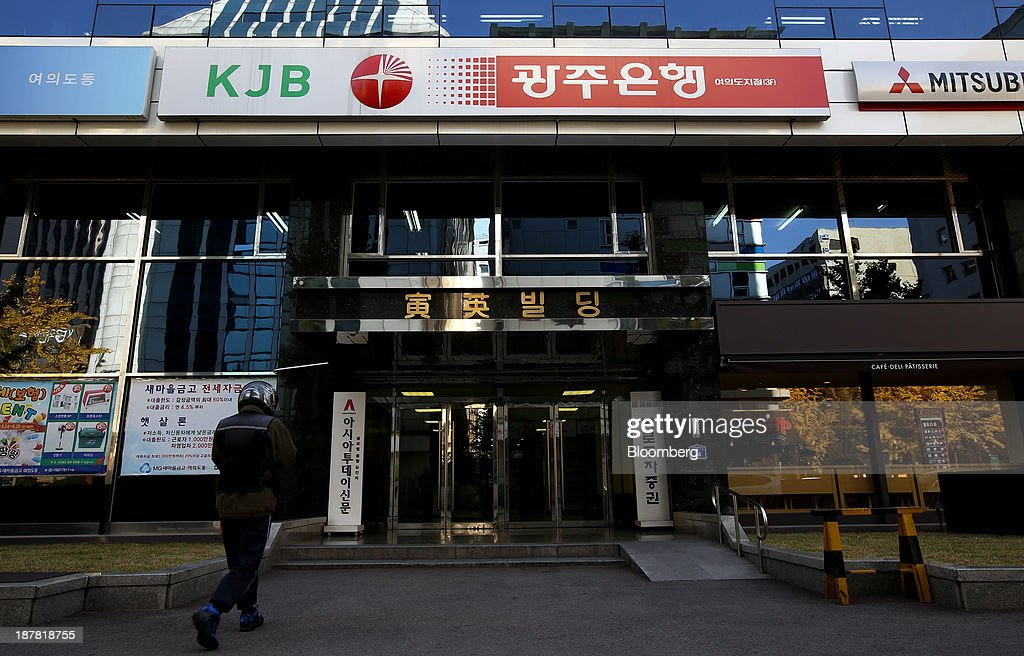 A man walks towards a building housing a branch of Kwangju Bank, a unit of Woori Finance Holdings Co., in Seoul, South Korea, on Tuesday, Nov. 12, 2013. Woori Finance Holdings is scheduled to report third-quarter results on Nov. 14. Photographer: SeongJoon Cho/Bloomberg via Getty Images