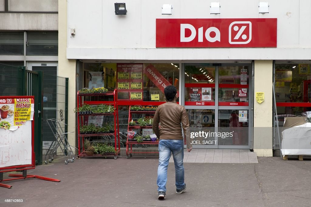 A man walks towards a Dia discount supermarket on May 8, 2014 in Paris. Spanish hard discount supermarket group Dia announced on May 8 it is selling its troubled French operations, which employ some 7,500 people in 900 stores. AFP PHOTO /JOEL SAGET