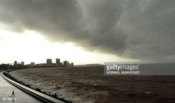 A man walks towards a sea wall on Marine Drive on the Arabian Sea front in Mumbai on July 23 as high tides lash the western Indian coast Civic...