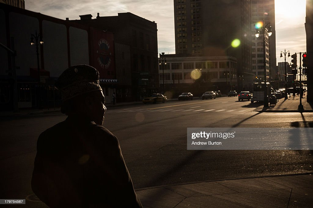 A man walks towards the sun set on September 6, 2013 in Detroit, Michigan. Detroit is struggling with over 78,000 abandoned homes across 140 square miles and 16% unemployment; in July, the city declared bankruptcy.