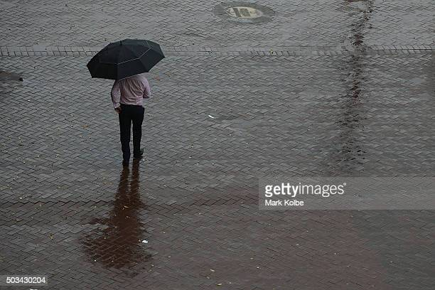 A man walks under an umbrella to shelter from the rain as he walks through Circular Quay on January 5 2016 in Sydney Australia Sydney has experienced...