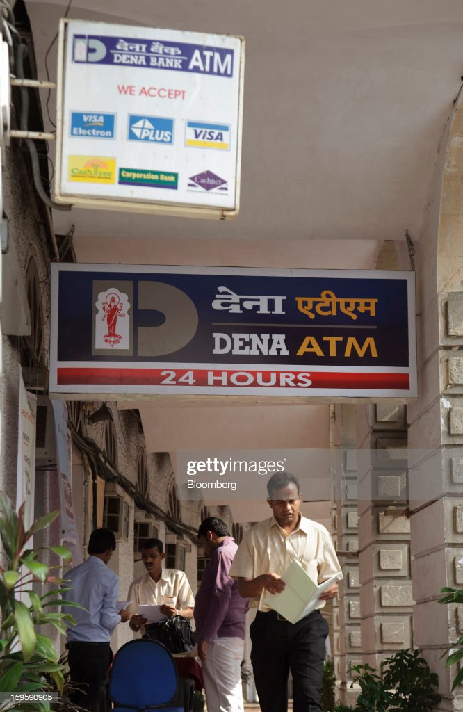 A man walks under signage for a Dena Bank automated teller machine (ATM) in Mumbai, India, on Wednesday, Jan. 16, 2013. India's financial system has been made vulnerable by a deterioration in bank assets and a lack of capital as the economy slowed, according to the International Monetary Fund. Photographer: Kuni Takahashi/Bloomberg via Getty Images