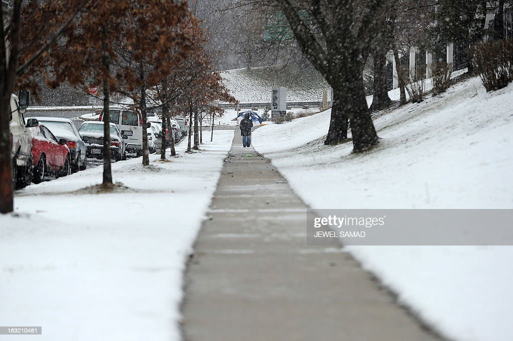 A man walks under snowfall in Silver Spring, Maryland, on March 6, 2013. A massive winter storm pounding the northern US on March 6, grounded 2,600 flights, closed hundreds of schools and made roadways and highways impassible. At least four people were reportedly killed in accidents on icy and snow covered roads and highways. AFP PHOTO/Jewel Samad
