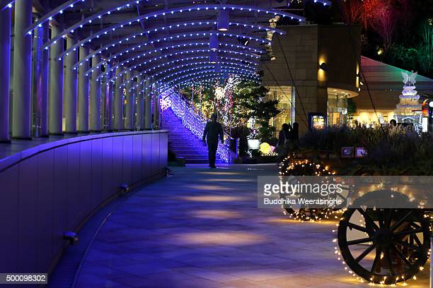 A man walks under the Christmas decorations and lights at the office and shopping complex in Namba Park on December 5 2015 in Osaka Japan Christmas...