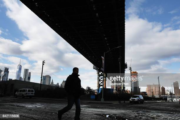 A man walks under the Manhattan Bridge on February 16 2017 in New York City An annual report by the American Road and Transportation Builders...