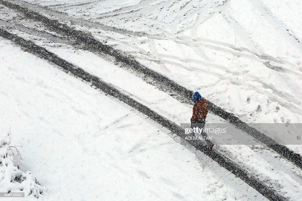 A man walks under the snow in Ankara on February 6, 2016. / AFP / ADEM ALTAN