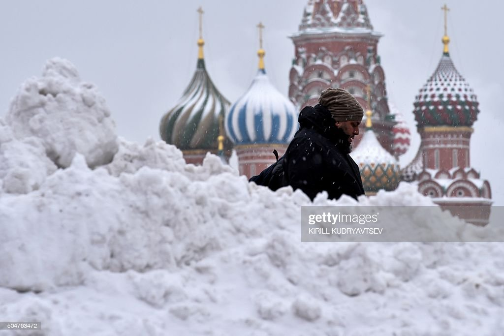 A man walks under the snow past St. Basil's Cathedral on Moscow's Red Square on January 13, 2016. / AFP / KIRILL