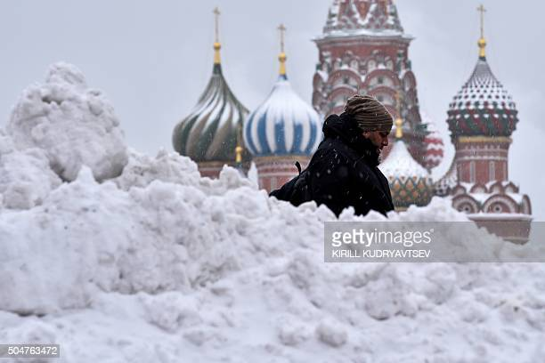 A man walks under the snow past St Basil's Cathedral on Moscow's Red Square on January 13 2016 / AFP / KIRILL KUDRYAVTSEV