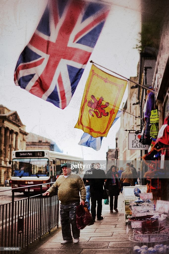 A man walks under Union Jack and Lion Rampant flags on April 23, 2014 in Edinburgh, Scotland. A referendum on whether Scotland should be an independent country will take place on September 18, 2014.