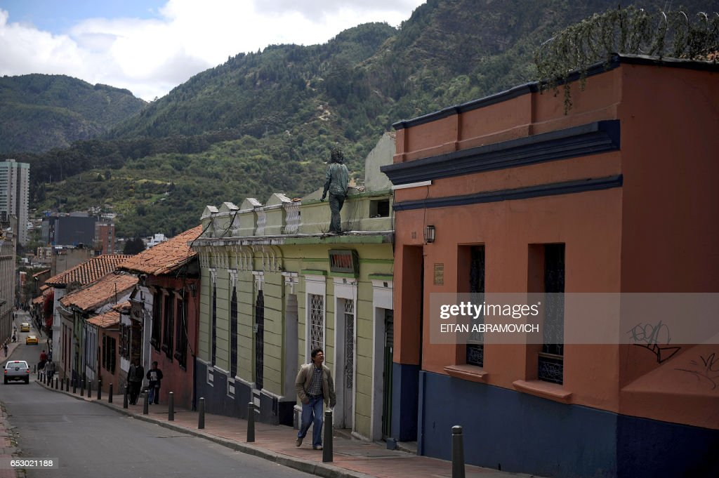 A man walks up a street of the historic neighborhood of La Candelaria in Bogota on September 17, 2009. La Candelaria is Bogota's oldest neighbourhood and the city's historical center, known for its colonial houses with wooden balconies and clay shingle roofs. AFP PHOTO/Eitan Abramovich /