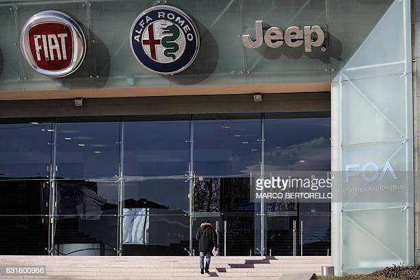 A man walks up stairs as the logos of automobile companies Fiat Alfa Romeo and Jeep are pictured at the entrance to the Fiat Chrysler Automobiles at...
