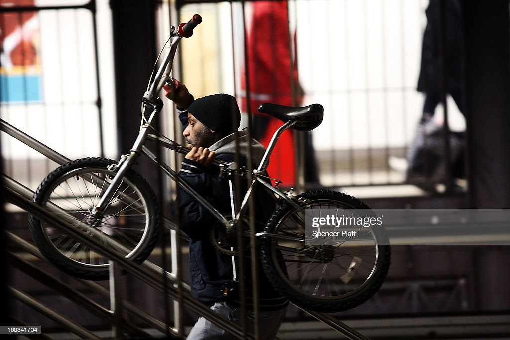 A man walks up stairs with his bike after exiting a subway at a Manhattan station on January 29, 2013 in New York City. The city has been experiencing a rash of high-profile incidents involving individuals being hit by trains in suicides, accidents and people being pushed to their deaths. Lawmakers are planning to discuss the recent deaths while also seeking ideas for more safety on the tracks. The New York City subway system, with 468 stations in operation, is the most extensive public transportation system in the world. It is also one of the world's oldest public transit systems, with the first underground line of the subway opening on October 27, 1904.