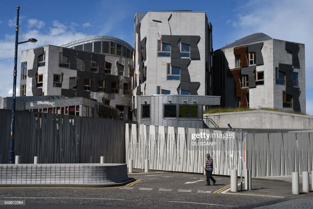 A man walks walks past the Scottish Parliament building in Edinburgh, Scotland on June 25, 2016. Scotland wants immediate talks with the European Union on protecting its place in the bloc, after Britain's vote to leave the EU, First Minister Nicola Sturgeon said Saturday. Speaking after an emergency meeting of her cabinet, Sturgeon said it had agreed to seek 'immediate discussions with the EU institutions and other EU member states to explore all possible options to protect Scotland's place in the EU.' SCARFF