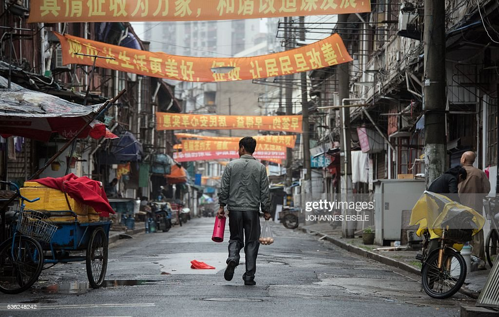 A man walks with a bag of eggs and a tea can along a street in Shanghai on June 1, 2016. Activity in Chinese factories expanded for the third straight month in May, official data showed, a further sign of stabilisation in the world's second largest economy. / AFP / JOHANNES