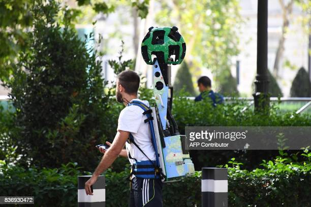 A man walks with a Google Street View Trekker backpack camera in Madrid on August 22 2017 / AFP PHOTO / GABRIEL BOUYS