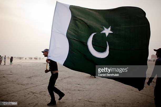 A man walks with a Pakistan National flag as people gather at Seaview waterfront to celebrate Pakistan's Independence Day on August 14 2011 in...