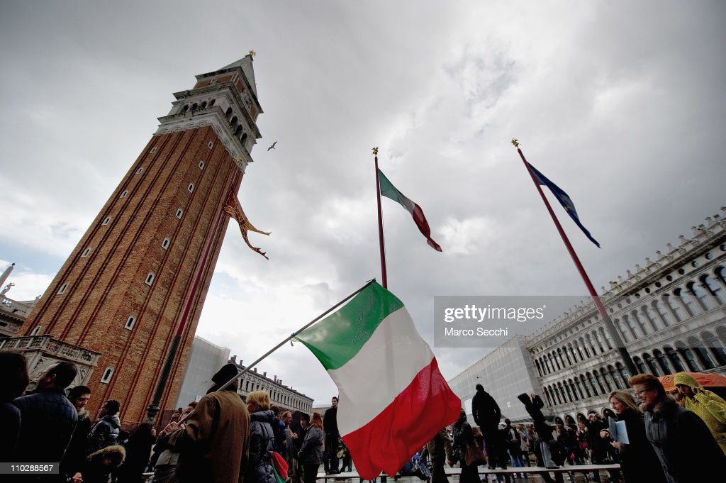 A man walks with an Italian national flag in St Mark Squar on the day of the celebrations for the 150th anniversary of Italy's unification on March 17, 2011 in Venice, Italy. Events in various Italian cities will celebrate the 150th anniversary of Italy's unification until the end of the year. National Festivity begins on March 17.
