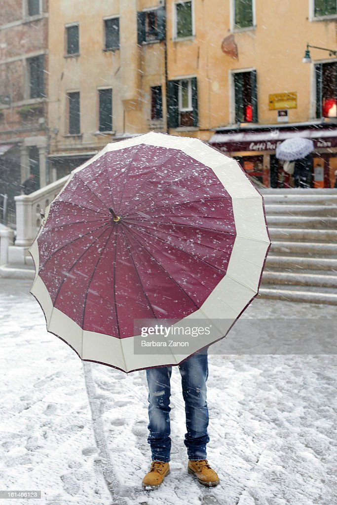 A man walks with an umbrella in Campo dei Frari during heavy snow on February 11, 2013 in Venice, Italy. Heavy snow, rain and wind hit the canals as boats moved commuters across the islands.