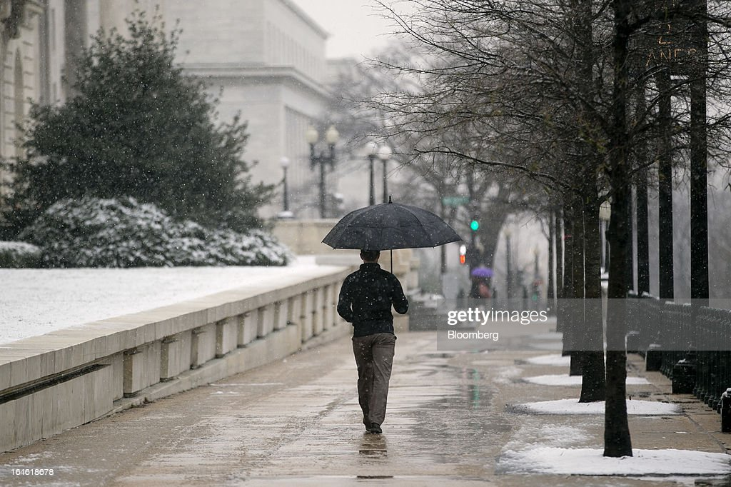 A man walks with an umbrella past the Canon House Office Building in Washington, D.C., U.S., on Monday, March 25, 2013. An early spring snowstorm tied up air traffic along the U.S. East Coast, threatening to bring 3 inches (7.6 centimeters) of slushy snow to the large cities from Washington to New York. Photographer: Andrew Harrer/Bloomberg via Getty Images