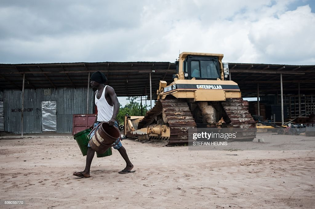 Man On Bulldozer : A man walks with empty buckets after refuelling