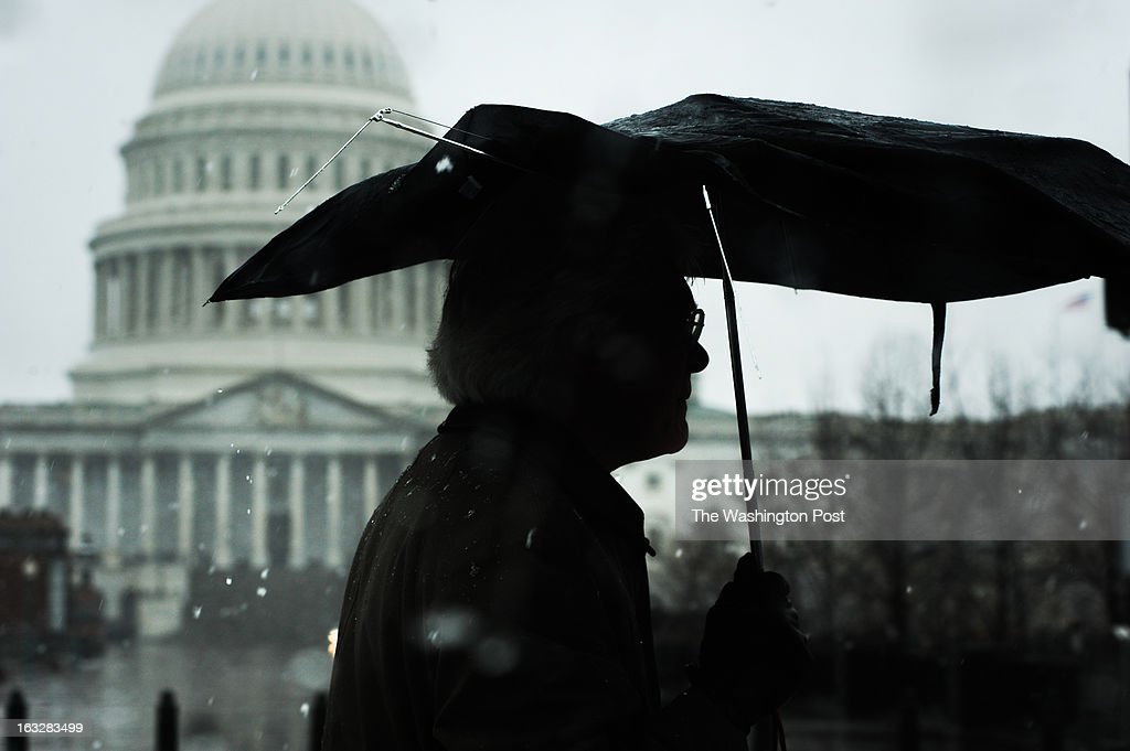 A man walks with his broken umbrella across North Capitol street with the Capitol building in background during the Snowquester in Washington DC. March, 06, 2013 in Washington, DC.